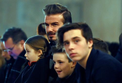 British soccer player David Beckham and his children attend his wife Victoria Beckham's show during the Fall 2016 New York Fashion Week on February 14, 2016, in New York. / AFP / Jewel SamadJEWEL SAMAD/AFP/Getty Images