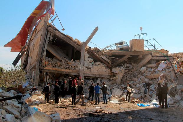 People gather around the rubble of a hospital supported by Doctors Without Borders (MSF) near Maaret al-Numan, in Syria's northern province of Idlib, on Febrary 15, 2016, after the building was hit by air strikes