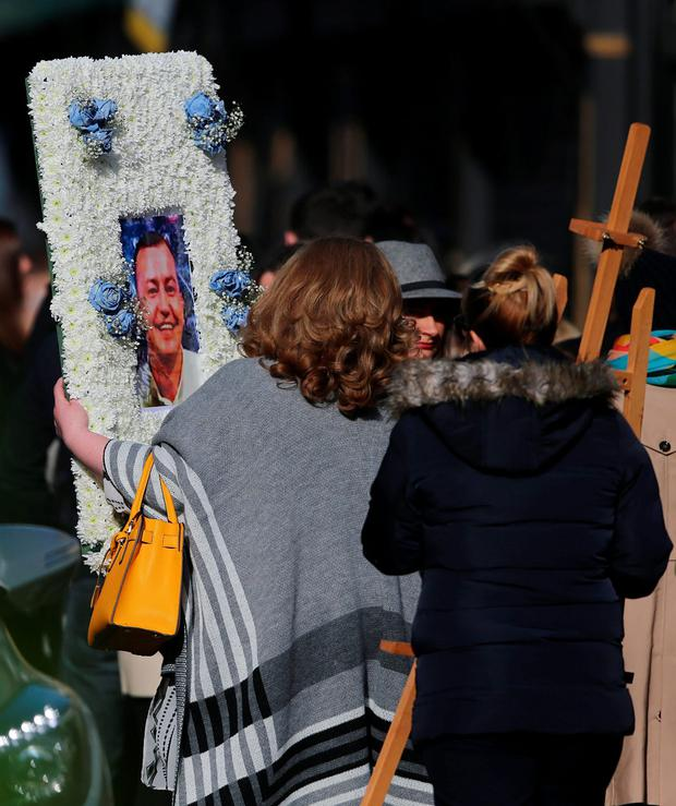 A floral tribute with a photograph of David Byrne is carried by a mourner into St Nicholas of Myra church on Francis Street in Dublin, ahead of his funeral, after he was shot dead during a boxing weigh-in at the Regency Hotel in the north of the city on Friday February 5 by a six strong gang, some armed with assault rifles. Niall Carson/PA Wire