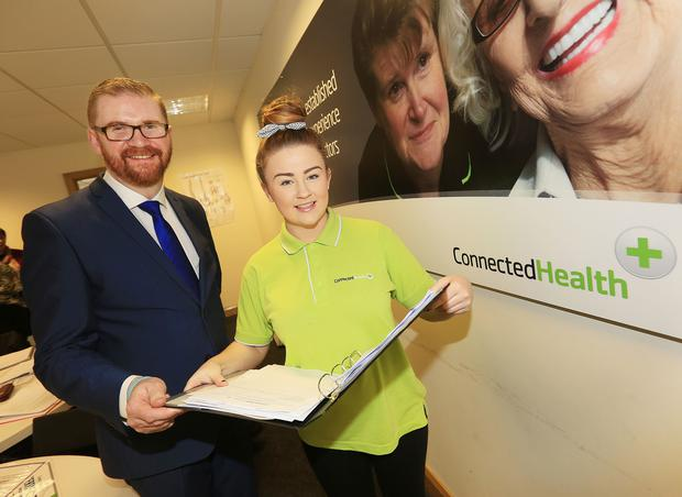 Health Minister Simon Hamilton with Care Worker Caitlin Boyle receiving her Care Induction Completion Certificate at the launch of the Connected Health Training Suite.