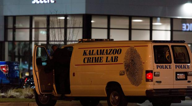 An officer with the Kalamazoo Crime Lab leaves the scene of a random shooting on Sunday, Feb. 21, 2016 in Kalamazoo.