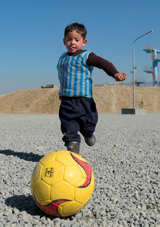 In this file photograph taken on February 1, 2016, Afghan boy five-year-old Murtaza Ahmadi, a young Lionel Messi fan, plays football in Kabul. Argentine football star Lionel Messi has sent not one, but two jerseys to the five-year-old Afghan boy who became an Internet sensation last month when he was pictured wearing a plastic bag with