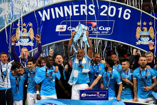 Just champion: City's Vincent Kompany lifts the League Cup