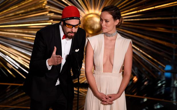 Actor Sacha Baron Cohen (L) and Olivia Wilde speak on stage at the 88th Oscars on February 28, 2016 in Hollywood, California. AFP PHOTO / MARK RALSTONMARK RALSTON/AFP/Getty Images