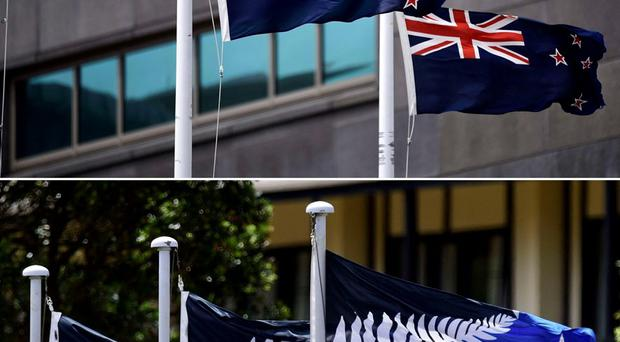 The current New Zealand flag hoisted outside a Te Papa museum and (bottom) the alternative flag to the current New Zealand flag hoisted outside a hotel. New Zealanders began voting on March 3 on whether to adopt a new flag. AFP PHOTO / FILES / MARTY MELVILLEMarty Melville/AFP/Getty Images