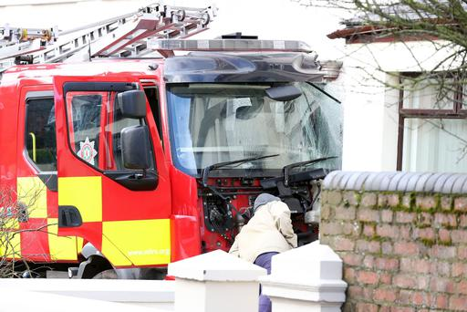 Two men aged 66 and 19 are being questioned by police about the theft of a fire engine. Above: The scene on the Glenarm Road in Larne where a fire engine which had been stolen from the town's fire station during the night crashed into a number of cars and houses. 5 March 16 - Picture by Darren Kidd / Press Eye.