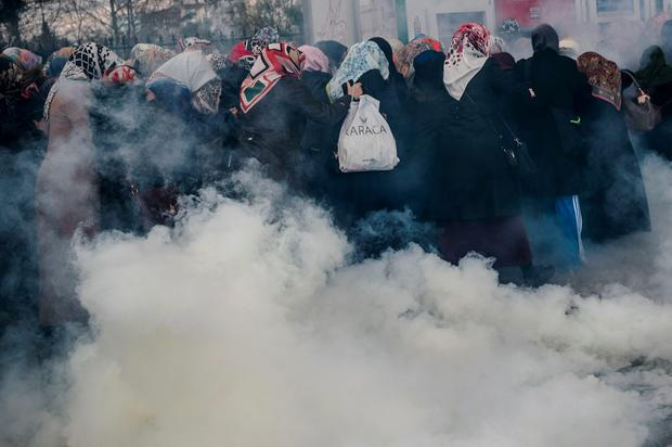 Women run as Turkish anti-riot police officers use tear gas to disperse supporters in front of the headquarters of the Turkish daily newspaper Zaman in Istanbul on March 5, 2016, after Turkish authorities seized the headquarters in a midnight raid. AFP/Getty Images