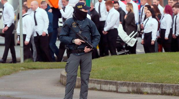 Armed Garda look on as the coffin of dissident republican Vincent Ryan is carried into The Church of the Holy Trinity in Donaghmede, Dublin, for his funeral Mass.