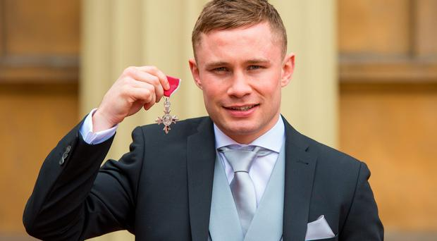 Boxer Carl Frampton holds his Member of the British Empire (MBE) medal which was awarded by the Duke of Cambridge at an investiture ceremony at Buckingham Palace, London. Dominic Lipinski/PA Wire