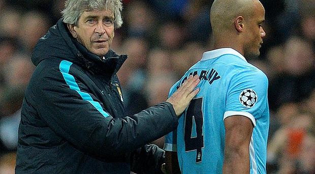 Manchester City's Chilean manager Manuel Pellegrini (L) consoles Manchester City's Belgian defender Vincent Kompany as he leaves the pitch injured during a UEFA Champions League last 16, second leg football match between Manchester City and Dynamo Kiev at the Etihad Stadium in Manchester, north west England, on March 15, 2016. / AFP PHOTO / OLI SCARFFOLI SCARFF/AFP/Getty Images