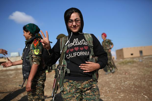 A female soldier from the Syrian Democratic Forces stands with fellow troops at a forward operating base on November 10, 2015 near the ISIL-held town of Hole in the autonomous region of Rojava, Syria. (Photo by John Moore/Getty Images)