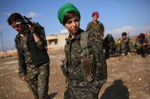Kurdish female troops from the Syrian Democratic Forces stand in a forward operating base overlooking the frontline on November 10, 2015 near the ISIL-held town of Hole in the autonomous region of Rojava, Syria. (Photo by John Moore/Getty Images)
