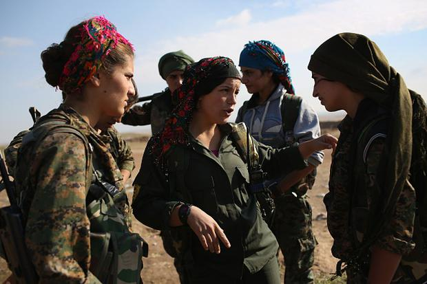 Kurdish female troops from the Syrian Democratic Forces speak in a forward operating base overlooking the frontline on November 10, 2015 near the ISIL-held town of Hole in the autonomous region of Rojava, Syria. (Photo by John Moore/Getty Images)
