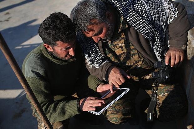 Kurdish commanders from the Syrian Democratic Forces coordinate frontline troop movements with the aid of a tablet at a forward operating base on November 10, 2015 near the ISIL-held town of Hole in the autonomous region of Rojava, Syria. (Photo by John Moore/Getty Images)