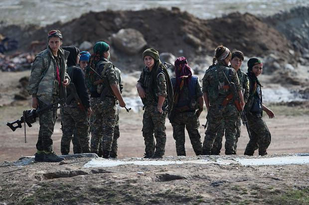 HOLE, SYRIA - NOVEMBER 10: Female troops from the Syrian Democratic Forces discuss frontline positions from a forward operating base on November 10, 2015 near the ISIL-held town of Hole in the autonomous region of Rojava, Syria. The coalition of forces, primarily Kurdish, are attacking ISIL extremists in the area near the Iraqi border and calling in airstrikes from U.S.-led coalition warplanes. The autonomous region of Rojava in northern Syria has become a bulwark against the Islamic State. The Rojava armed forces, with the aid of U.S. airstrikes and weapons, are retaking territory which had earlier been captured much by ISIL from the Syrian regime. (Photo by John Moore/Getty Images)