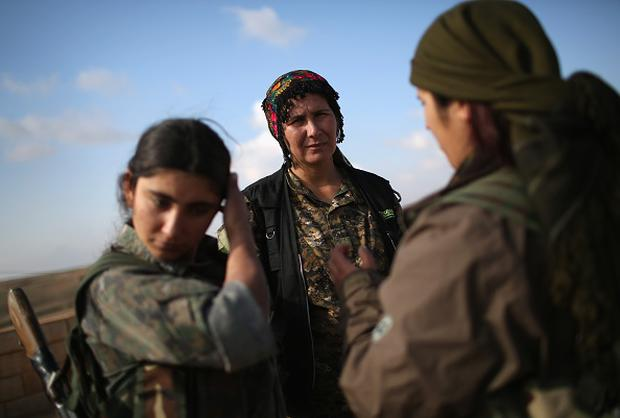 Soldiers from the Syrian Democratic Forces discuss frontline movements from a forward operating base on November 10, 2015 near the ISIL-held town of Hole in the autonomous region of Rojava, Syria. (Photo by John Moore/Getty Images)