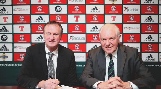 Pen to paper: Michael O'Neill signs his new four-year contract yesterday as Irish FA President Jim Shaw looks on