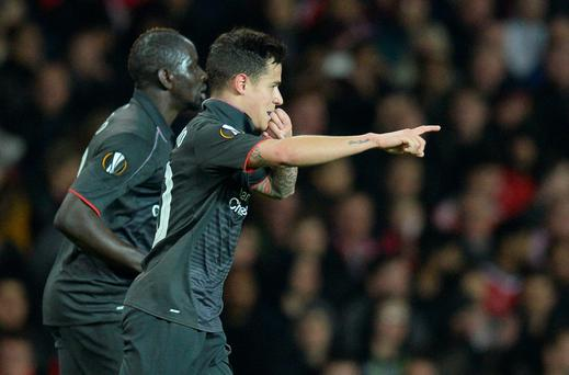 Liverpool's Brazilian midfielder Philippe Coutinho (R) celebrates after scoring their first goal during the UEFA Europa League round of 16, second leg football match between Manchester United and Liverpool at Old Trafford in Manchester, north west England on March 17, 2016. / AFP PHOTO / OLI SCARFFOLI SCARFF/AFP/Getty Images