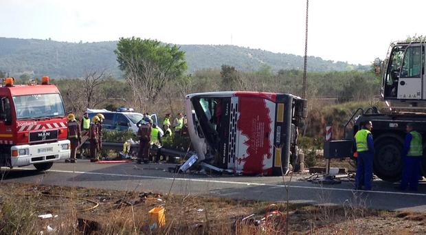 Emergency services personnel stand at the scene of a bus accident crashed on the AP7 highway that links Spain with France along the Mediterranean coast near Freginals halfway between Valencia and Barcelona early Sunday, March 20, 2016. The bus was reportedly hired out to carry students to and from a fireworks festival in Valencia and was on the return leg of its journey when the accident happened. (AP Photo)