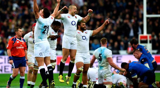 Jumping for joy: Mike Brown leads the celebrations as England wrap up their Grand Slam