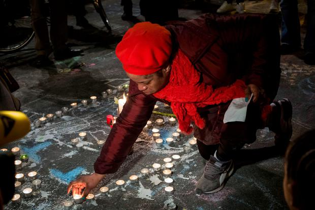 A woman lights a candle among floral tributes and notes in front of the Bourse of Brussels on March 22, 2016 in tribute to the victims of Brussels following triple bomb attacks in the Belgian capital that killed about 35 people and left more than 200 people wounded. AFP/Getty Images