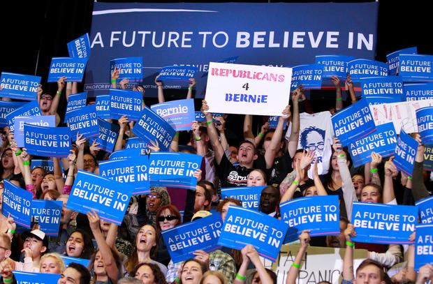 Supporters wave signs as Democratic presidential candidate Bernie Sanders speaks during a campaign rally at West High School on March 21, 2016 in Salt Lake City, Utah. The Republican and Democratic caucus will be held in Utah on Tuesday, March 22. (Photo by George Frey/Getty Images)