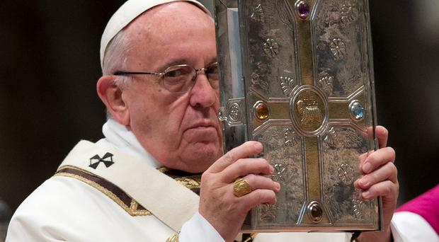 Pope Francis holds the Gospel book as he leads a Chrism Mass in St Peter's Basilica, Rome