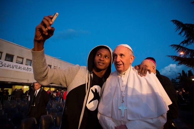 Pope Francis poses for a selfie with a refugee during his visit at the Castelnuovo di Porto refugees center near Rome on March 24, 2016. AFP/Getty Images