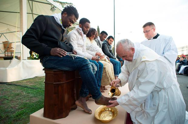 Pope Francis performs the foot-washing ritual at the Castelnuovo di Porto refugees center near Rome on March 24, 2016. Pope Francis washed the feet of 11 young asylum seekers and a worker at their reception centre to highlight the need for the international community to provide shelter to refugees. AFP/Getty Images