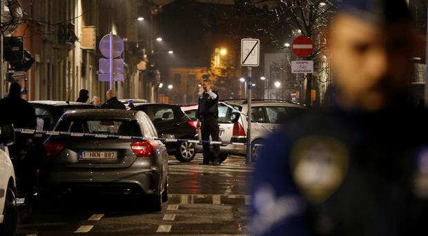 Police guard a check point and man positions during a police raid in the suburb of Schaerbeek in Brussels, early Friday, March, 25, 2016. (AP Photo/Alastair Grant)