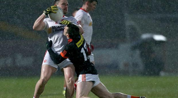 Within reach: Tyrone's Padraig Hampsey is closed down by Armagh's Stephen Sheridan