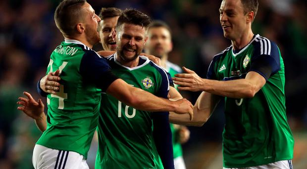 Northern Ireland's Conor Washington (left) celebrates scoring his side's first goal of the game with team mates Oliver Norwood and Jonathan Evans during an International Friendly at Windsor Park, Belfast. PA