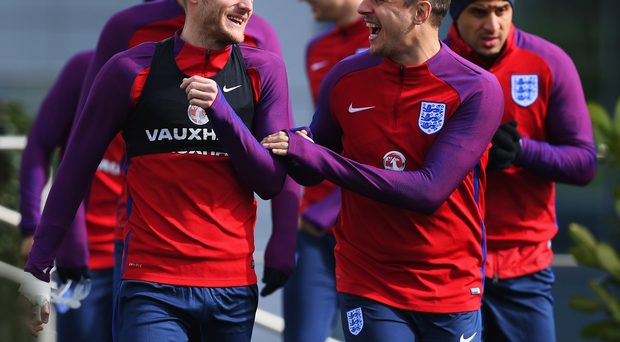 High spirits: Jamie Vardy shares a joke with Phil Jagielka during England training yesterday