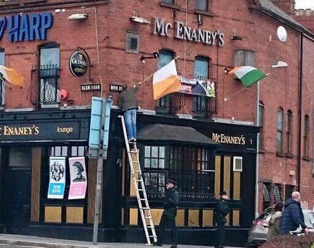 Social Media Image showing a PSNI officer holding a Ladder for a man raising a flag on the Falls road in Belfast.