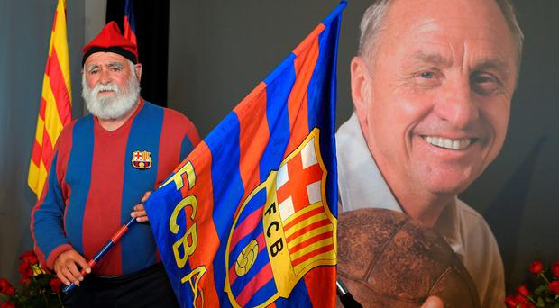 A FC Barcelona supporter poses as he pays tribute to late Dutch football star Johan Cruyff in a special condolence area set up at Camp Nou stadium, in Barcelona on March 29, 2016. AFP/Getty Images