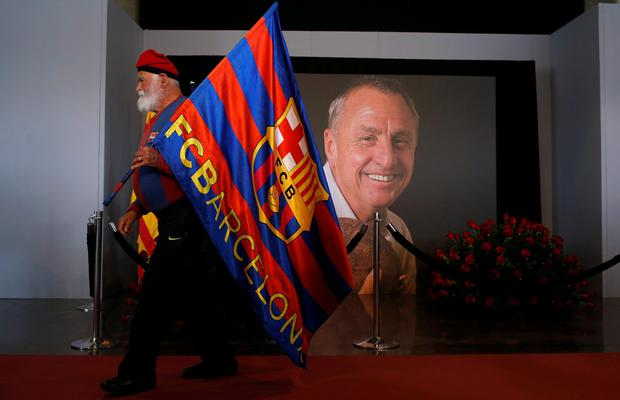 A FC Barcelona's supporter holds a FC Barcelona flag offering his respects as a photograph is displayed showing the late Dutch soccer Johan Cruyff at the Camp Nou stadium in Barcelona, Spain, Tuesday, March 29, 2016. Dutch soccer great Johan Cruyff, who revolutionized the game as the personification of