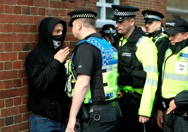 Police officers talk with a man at Dover Priory station in Dover, Kent, a head of a protest by far-right groups protesting against the arrival of immigrants and the Kent Anti-Racism Network, who have organised a counter-demonstration. PA