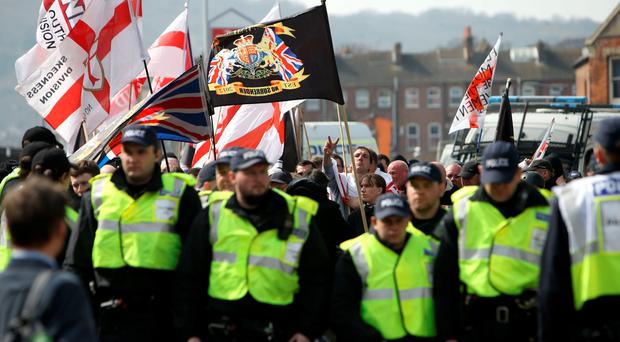 A line of police officers in front of a group of far-right protesters in Dover, Kent, who are protesting against the arrival of immigrants; the Kent Anti-Racism Network have also organised a counter-demonstration. PA