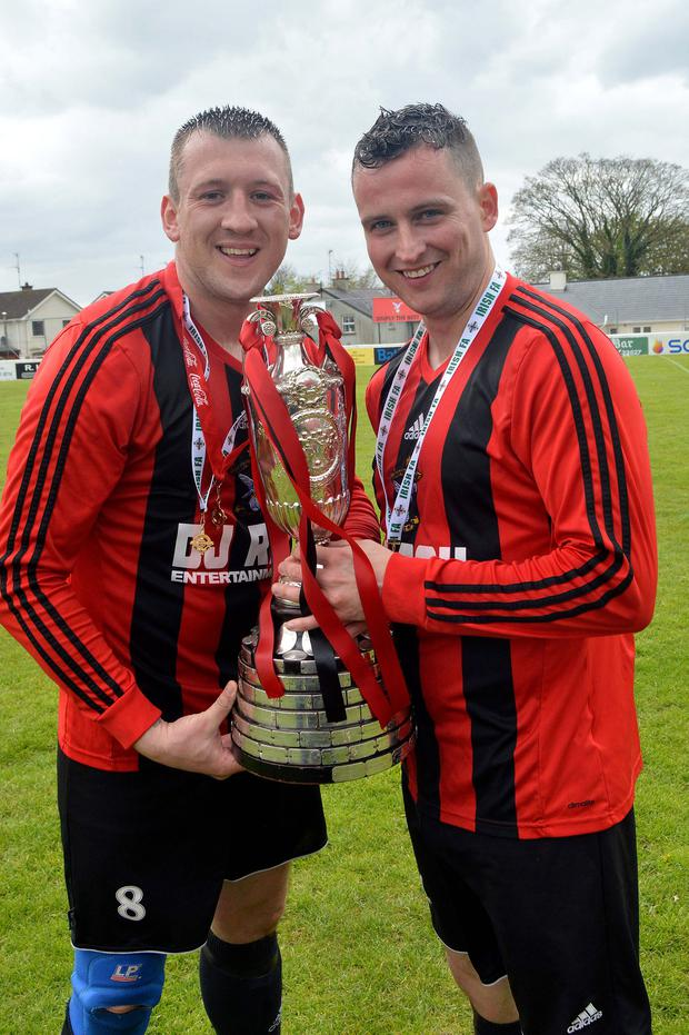 Harryville Homers captain Gary Bonnes and vice captain Ian Russell lift the Junior Cup after last year's final victory over Rosemount Rec. Both teams are into this year's semi-finals again