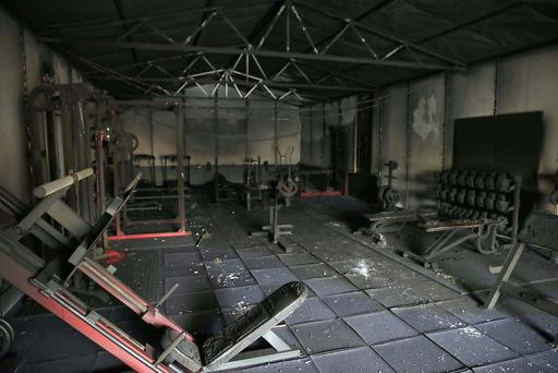 Connell Donnelly inside the gutted interior of his fitness suite at Moy GAA Club. A gym has been destroyed in a suspected arson attack at a GAA club in Moy, County Tyrone. Firefighters put out the fire that started at about 23:00 BST on Sunday. Extensive damage was caused to a new gym beside the Tír na nÓg clubhouse. The clubhouse was badly damaged in a similar attack in September 2015. PACEMAKER BELFAST 04/04/2016