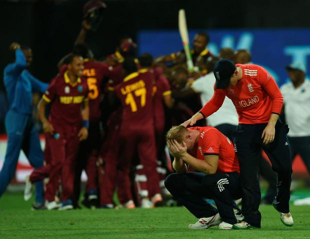 Joy and pain: England skipper Eoin Morgan consoles Ben Stokes as the West Indies celebrate their World T20 triumph