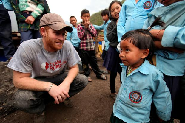 Prince Harry talks to a young boy during a visit to the Lapubesi temporary school site as he helps Team Rubicon UK carry out rebuilding work in March, 2016 in Lapubesi, Nepal. (Photo by Mauricio Gris/Team Rubicon UK via Getty Images)