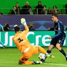Real Madrid's Portuguese forward Cristiano Ronaldo and Wolfsburg's Swiss goalkeeper Diego Benaglio vie for the ball