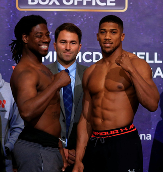 Seconds out: Promoter Eddie Hearn looks on as Anthony Joshua and Charles Martin square up during the weigh-in at The O2 Arena yesterday