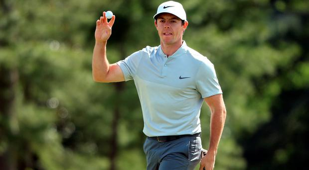 All in hand: Rory McIlroy salutes the crowd after holing a crucial putt at the 18th during his second round at the Masters