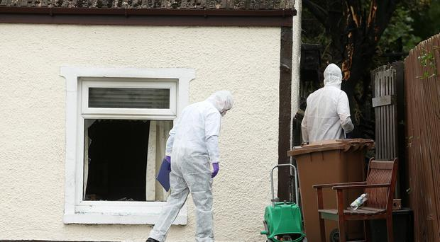 Forensic officers at the scene of Samuel Carson's home,