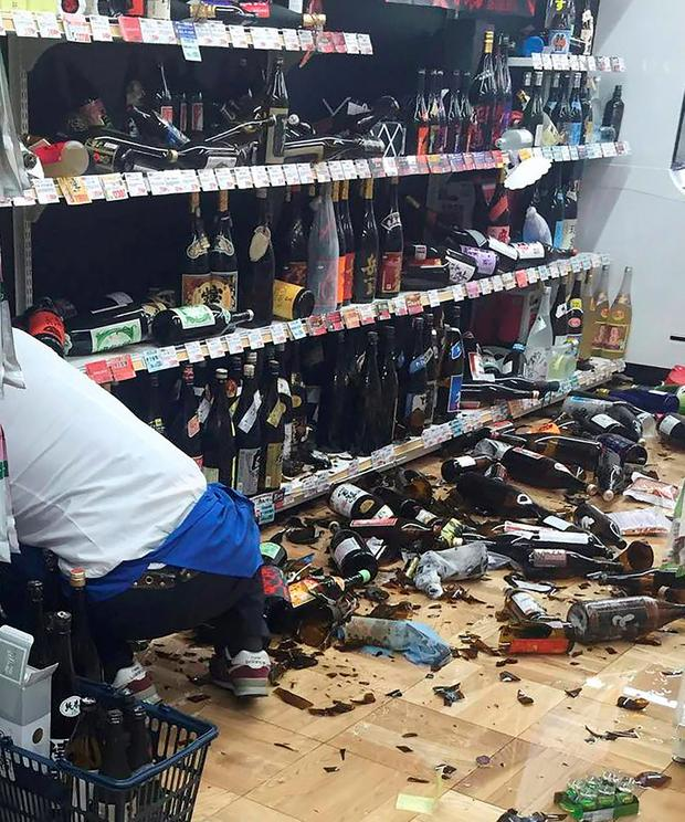 A shop clerk cleans broken wine bottles following an earthquake in Kumamoto city on April 14, 2016. AFP/Getty Images