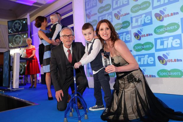 Oliver with Tony McGinn of Specsavers and The Fall star Bronagh Waugh after being presented with his award.