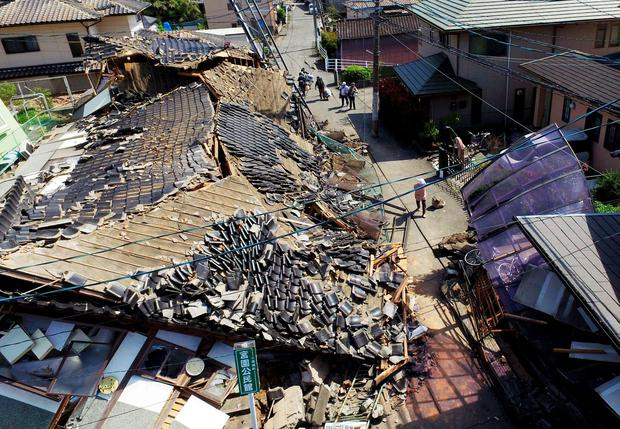 This aerial view shows damaged houses in Mashiki town, Kumamoto prefecture, southern Japan, Friday, April 15, 2016, a day after a magnitude-6.5 earthquake. (Koji Harada/Kyodo News via AP)