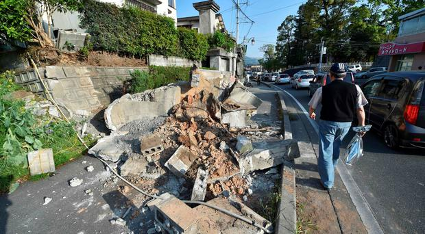 A man walks next to a sidewalk covered by rubble in Mashiki, Kumamoto prefecture on April 15, 2016, after a 6.5-magnitude quake struck the southwestern island of Kyushu on April 14. Rescuers searched through rubble for possible survivors on April 15 after a powerful earthquake in southern Japan left at least nine people dead and hundreds injured, though officials said the toll was unlikely to rise dramatically. / AFP PHOTO / KAZUHIRO NOGIKAZUHIRO NOGI/AFP/Getty Images